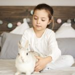 Girl and rabbit sitting on bed